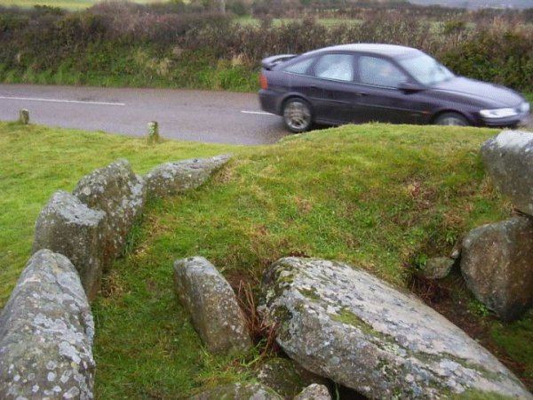 A road slices through one end of Tregiffian Burial Chamber in Cornwall.