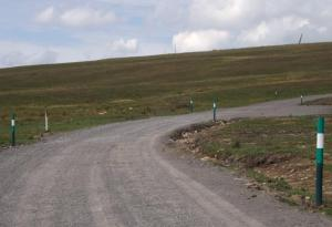 Bancbryn – new road and bollards. Turbine tips on skyline.