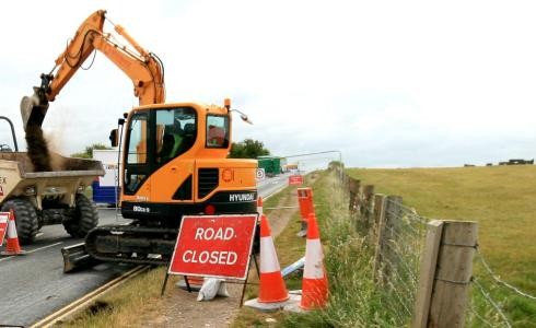 Digger at work on the former A344 in daylight within sight of the stones top right.