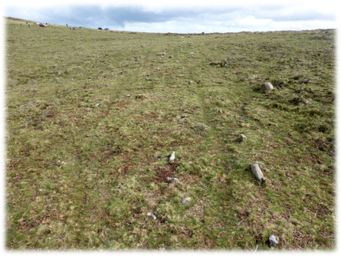 The three roughly parallel lines of stone can be traced up the hill towards the saddle.